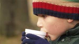 kid sipping hot chocolate